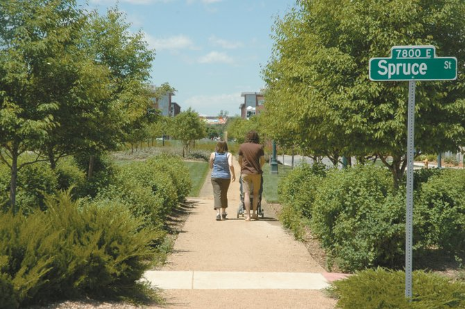 A young couple strolls with their child down a trail in the urban redevelopment of the former Stapleton International Airport in Denver. Steamboat Springs officials, developers, utility providers and members of the public toured the development Friday.
