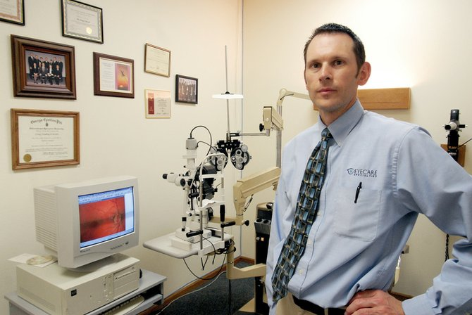 Optometrist Craig Eckroth, stands near a piece of eye exam equipment inside the offices of Eyecare Specialties, where he works. Eckroth is one of two optometrists in the office who offer eight vouchers each year to area elementary school students during the school year. The vouchers provide free eye exams and reduced-cost lenses and frames to students who need eye care, but whose parents cannot afford it.