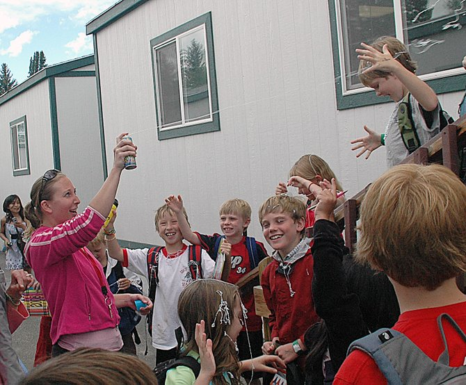 Soda Creek Elementary School third-grade teacher Rebecca Dybas sprays her students with silly string after the final bell sounded Friday afternoon.