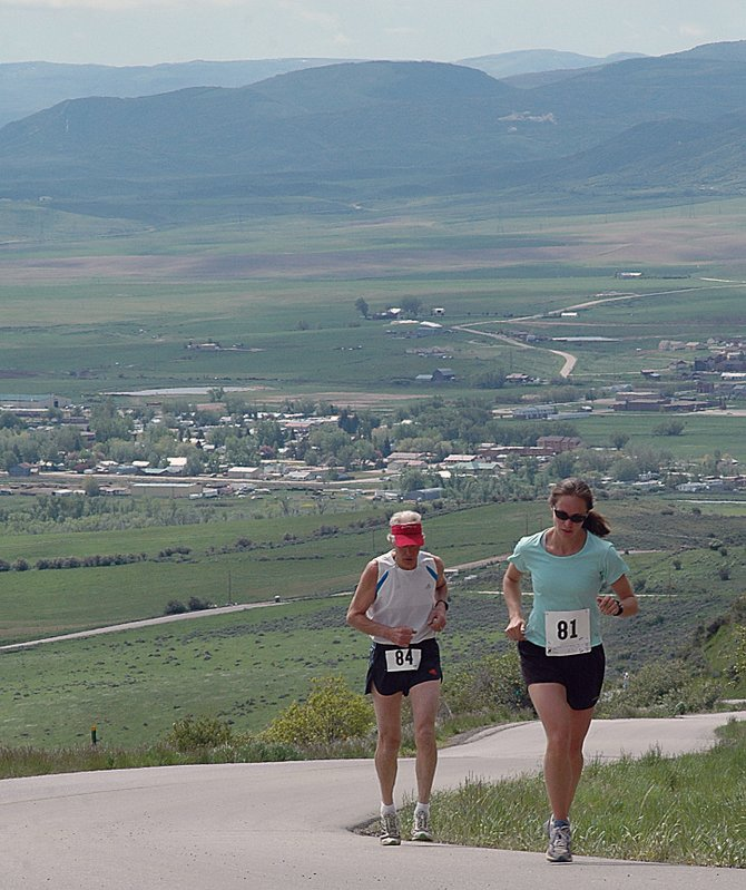 The town of Hayden lies in the background as Jenny Fox leads Thomas Nelson up Routt County Road 76 as a part of Saturday's Hayden Cog Run. The competitors ran 8.4 miles, from the Hayden City Park to the highest point on the Cog Road, then back again. Todd Trapp, of Craig, won the event in 54 minutes, 8 seconds.