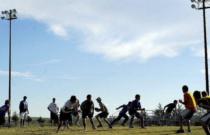 The Moffat County High School football team works on offensive drills Monday against Hayden High School. The team will get plenty of practice the next few days as they head to the University of Wyoming for football camp.