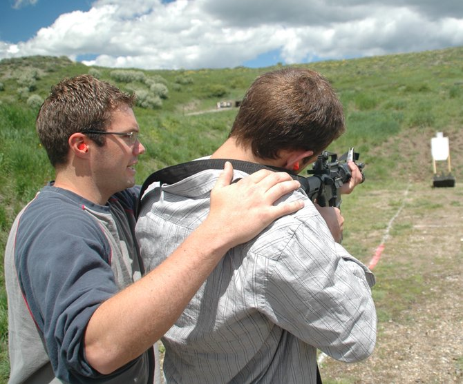 Steamboat Springs High School resource officer Josh Carrell helps junior Scott Frank on Friday afternoon as Frank prepares to fire an M-16 rifle at the shooting range west of Steamboat. A group of high school students spent their last day of classes before summer vacation at the range testing a robot they built to help area police officers in weapons training.