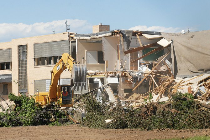 A heavy equipment operator goes to work on the Craig Middle School building Tuesday. The Neenan Company crews are scheduled to continue demolition on the building through July 4, project superintendent Doug Young said.