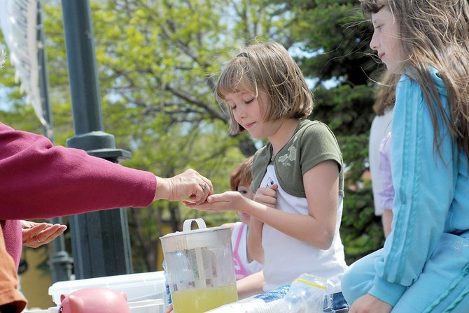 Allie Dilldine, left, 9, and Brittany Young, 10, sell lemonade Thursday at the Downtown Business Association's farmers market at Alice Pleasant Park. The trio was among a number of venders selling goods on the first day of the weekly event.