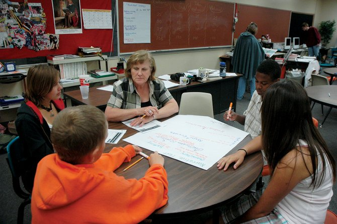 Moffat County High School teacher Katy Gray, center, helps students with reading skills Thursday at the Summer Reading Lab. Danielle Knez, 13, from right, Sean Johnson, 15, Colten Yoast, 11, and Terra Rieser, 15, listen in while Gray explains parts of a story.