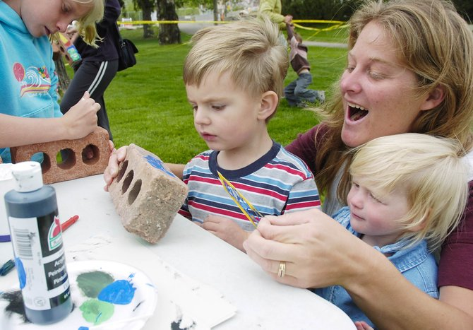 "Daycare provider Christina Ciufo holds her 2-year-old daughter, Hazel, while helping 2-year-old Trevor Harms stencil a brick Thursday at Lincoln Park across from the Bud Werner Memorial Library. Dozens of kids participated in decorating the bricks, which they were then able to take home for bookends. The library is hosting a summer reading program themed ""Building Excitement, Building Readers."""