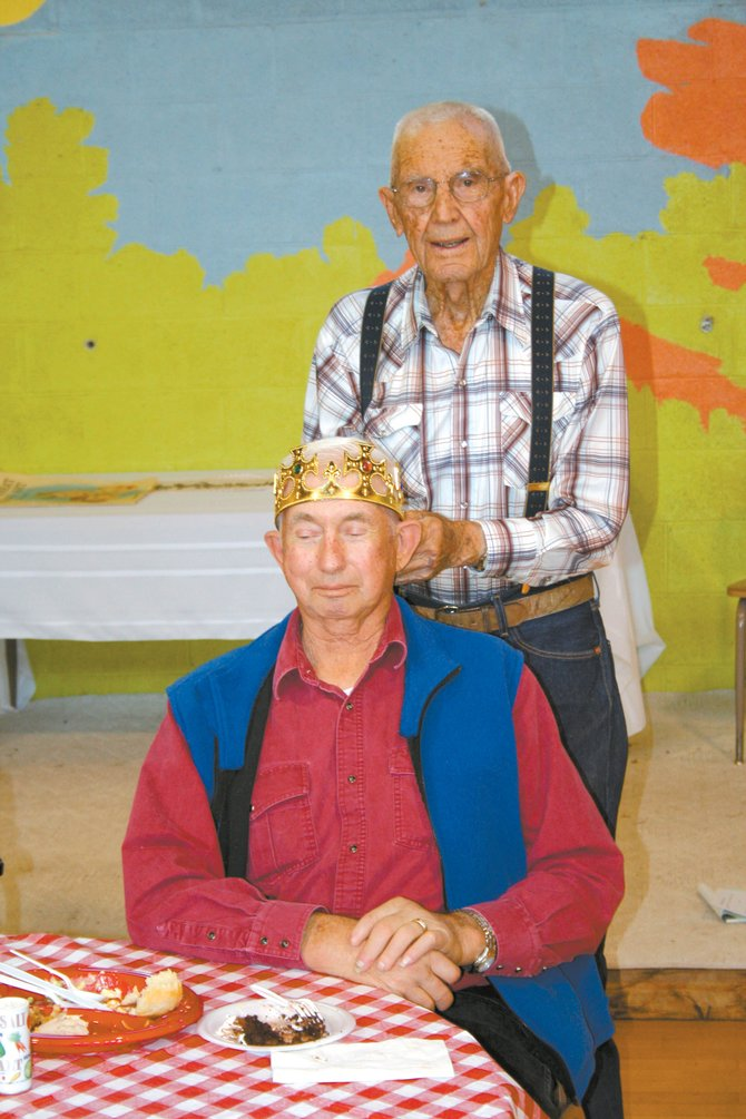 Bud Kier, 96, crowns 68-year-old Earl Harper, seated, as king of this year's Father's Day and Old-Timers Picnic on Sunday in McCoy. Kier is a previous king of the picnic and was recognized as the oldest attendee of Sunday's event.