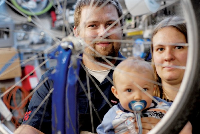 Aaron Ruybalid, his wife, Anna, and son, Titus, pose for a photo Thursday in their shop, J&R Cyclery. The Ruybalids have owned the store for four years.