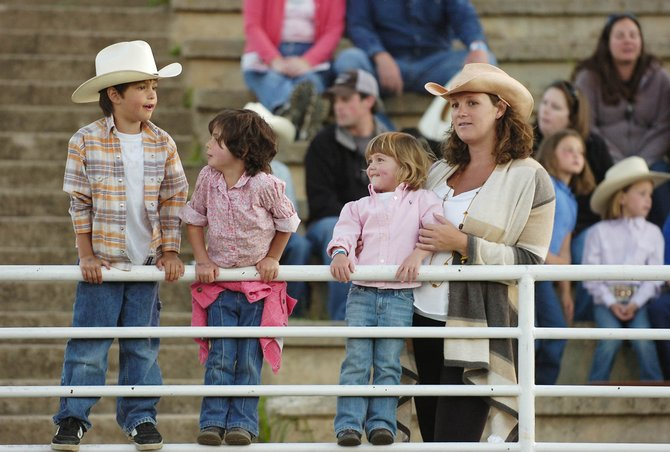 Steamboat Springs resident Ronni Collins holds her daughter Mia on a fence with Jake Alering and Alivia Thompson on June 13 at the Brent Romick Rodeo Arena.