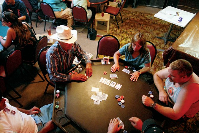 Larry Osborn, clockwise from left, Terri Reno and Bill Grover, wait for the river card Thursday during the Texas hold 'em tournament at the Popular Bar & Cafe. More than 20 players compete four days a week as part of Reno Poker in Craig.