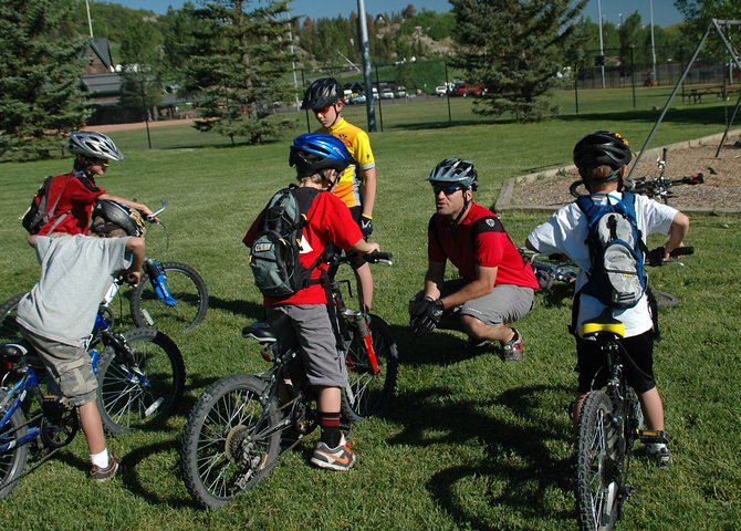 Biking coach Jon Casson talks to members of his group about bike safety before hitting the trails Thursday morning near Howelsen Hill. The group was a part of the Steamboat Springs Winter Sports Club&#39;s new youth mountain biking program, which will run for eight weeks during the summer.