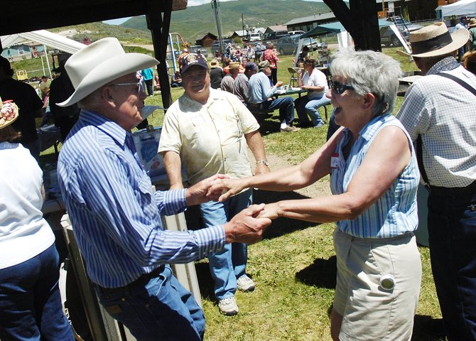 Longtime South Routt County residents Paul and Ellen Bonnifield dance in the food line Saturday at Phippsburg Community Park during the town's centennial celebration.