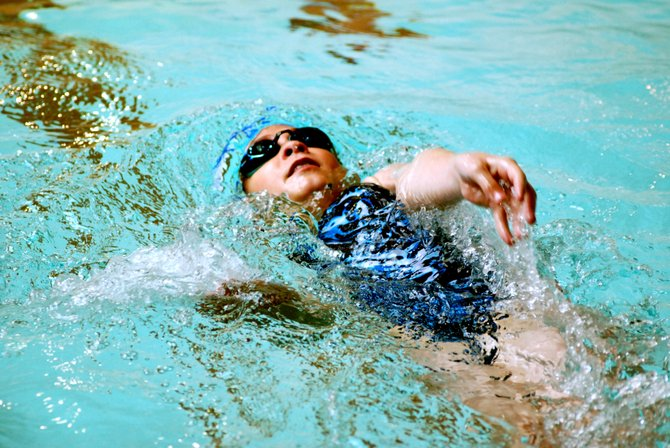 Bailey Kurz competes in the 50-meter backstroke two weeks ago in Rangely as part of the Craig Sea Sharks swimming team.