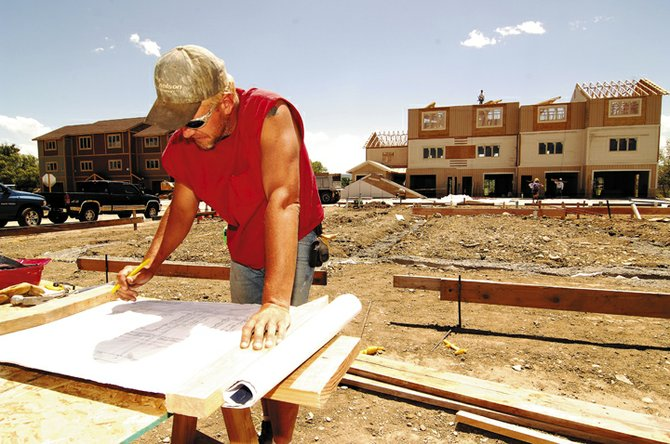 Construction worker Robert Area looks over plans Thursday at the Creekview development in Hayden.