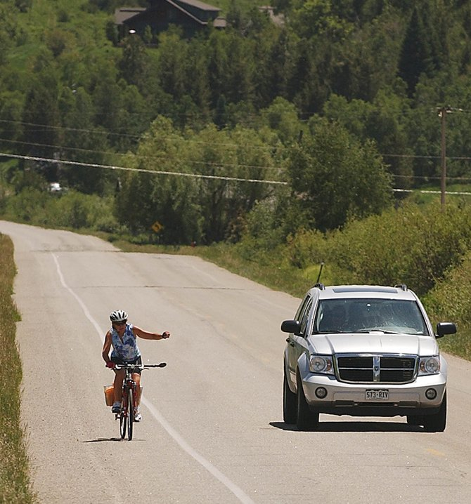 "Steamboat Springs resident Holly Williams signals a left turn into Perry-Mansfield Performing Arts School on Thursday off Routt County Road 36. Williams said she feels safe biking on the road but was ""not very happy"" about the planned narrowing of the road's shoulder."