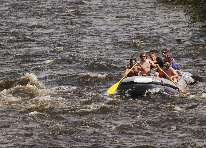 A group of rafters takes on the Yampa River on Tuesday afternoon in downtown Steamboat Springs. Backdoor Sports owner Pete Van De Carr says the Yampa is flowing too fast for tubing season to begin. 