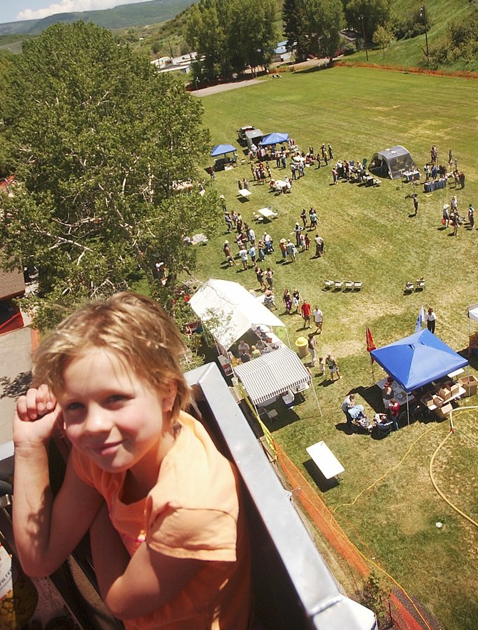 Eight-year-old Greta Thurston gets a bird's-eye view of the Taste of South Routt from a fire truck ladder bucket Saturday afternoon at Decker Park.