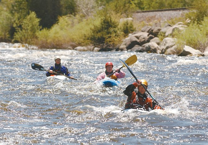 Team River Runner volunteer Jason Beakes, right, veteran Jennifer Jones, middle, and Troy Crawford with Team River Runner kayak down the Yampa River on Thursday afternoon.