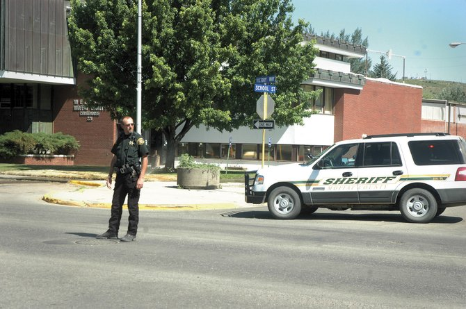 Cpl. Todd Wheeler of the Moffat County Sheriff's Office directs traffic Tuesday morning outside the Moffat County Courthouse. The courthouse was evacuated due to a gas leak.