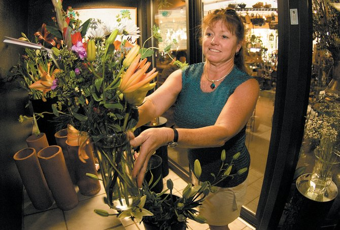 Steamboat Floral and Gifts employee Donna Segale places flowers inside one of the store's coolers. High gas prices have impacted business and changed the way the store makes deliveries and does business.