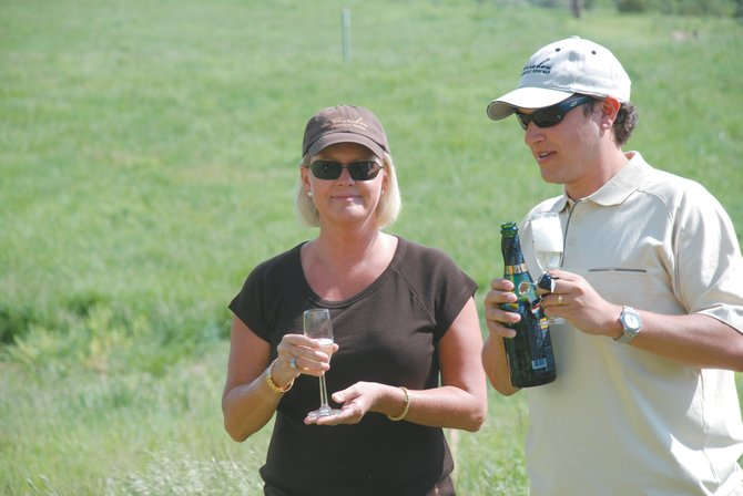 Anthony, right, and Lori Rivera share a champagne toast at the site of their new home in Marabou.