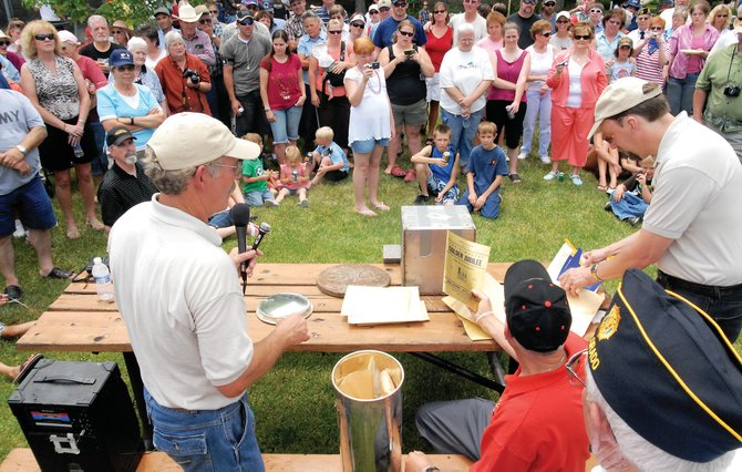 A large crowd watches as Museum of Northwest Colorado Director Dan Davidson, right, introduces items pulled out off Craig's 1958 time capsule Friday at City Hall. The crowd gathered at noon for the capsules' opening.