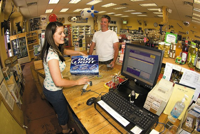 Arctic Liquors clerk Cathy McMunn rings up Bing Satre on Thursday afternoon in the store west of downtown Steamboat Springs. A new state law that went into effect this week means liquor stores can now be open on Sundays.