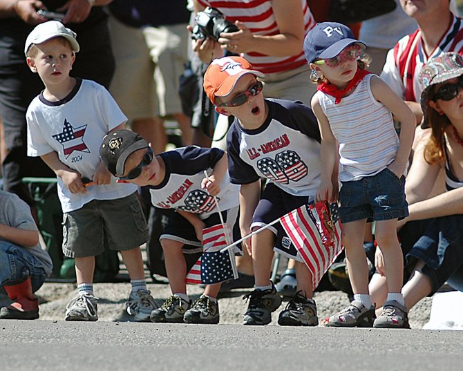In town to visit their grandma, T.J. St. Clair, from left, Ian Faussett, Nolan Faussett and Ellie St. Clair lean out from the sidewalk to catch a glimpse of Friday's Fourth of July parade on Lincoln Avenue in Steamboat Springs. Hundreds crowded the street Friday morning as floats and performance groups passed by.