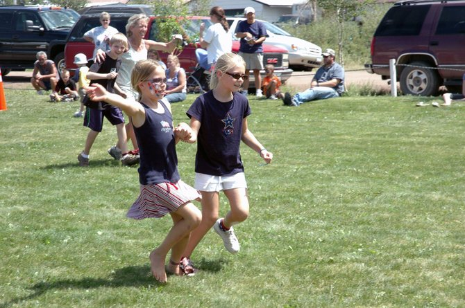 Ten-year-old Kail Constine, of Phippsburg, left, and 9-year-old Sophia Buntin, of Highland Park, speed toward the finish line Friday during the three-legged race at Yampa's Fourth of July celebration.