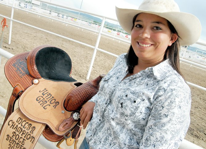 Gabbi Steele stands Sunday with the saddle she won at the Moffat County Little Britches Rodeo at the Moffat County Fairgrounds. Steele, in her last year of junior girls competition, won her second career saddle.