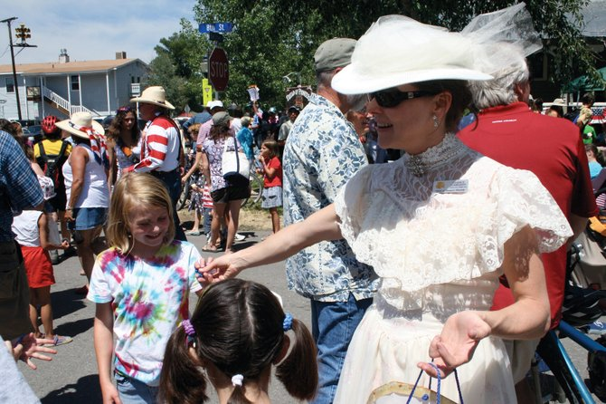 Candice Lombardo, executive director of the Tread of Pioneers Museum, gave away toys to children during the Pioneer Day Block Party on Friday.