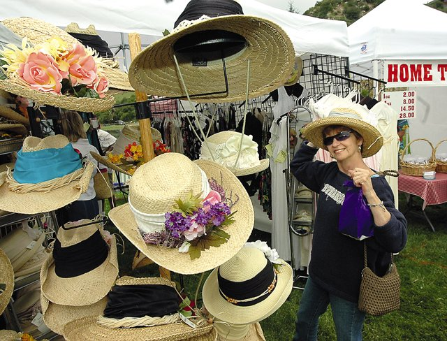 Anne Pixler of Denver stops to try on a straw hat during an Art in the Park event in Steamboat Springs. This year's event is from 9 a.m. to 5 p.m. Saturday and from 9 a.m. to 4 p.m. Sunday.