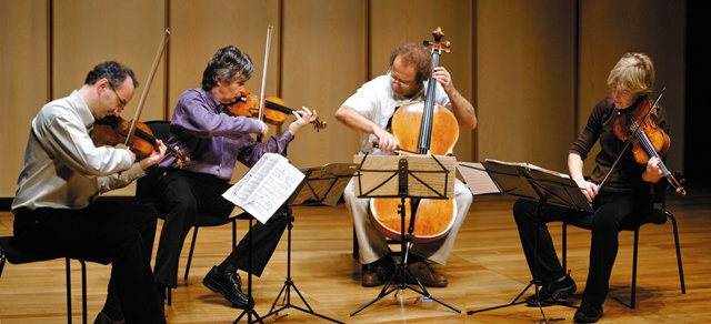 Takcs Quartet, made up of Edward Dusinberre, from left, Karoly Schranz, Andras Fejer and Geraldine Walther play at Queen Elizabeth Hall in London in February 2007. Below: The group poses more casually.