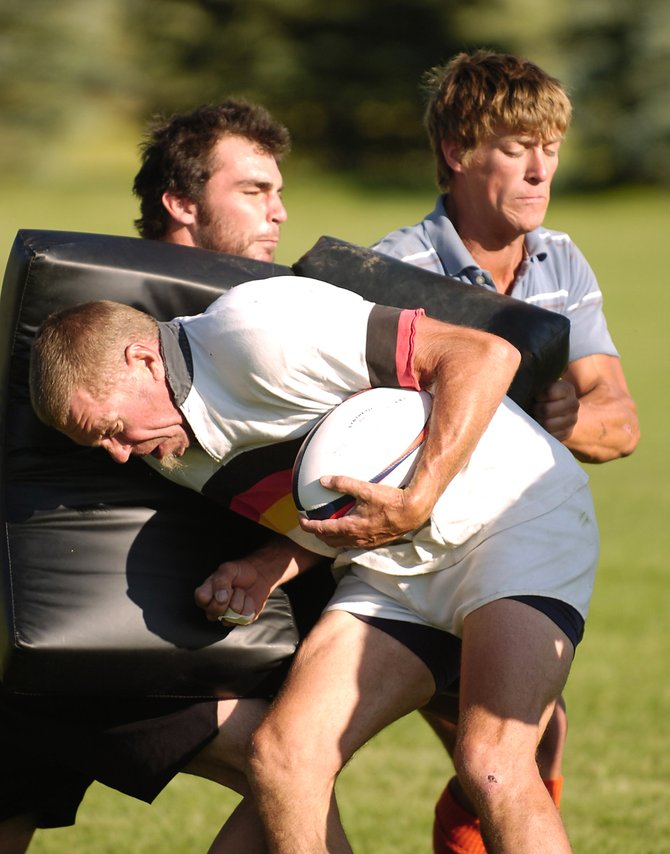 "Steamboat Springs rugby player Steve ""Zog"" Herzog plows into Richard Loop, right, and Erik Wernig on Thursday during practice at Whistler Field. The 34th annual Cow Pie Classic Rugby Tournament begins at 9 a.m. Saturday."