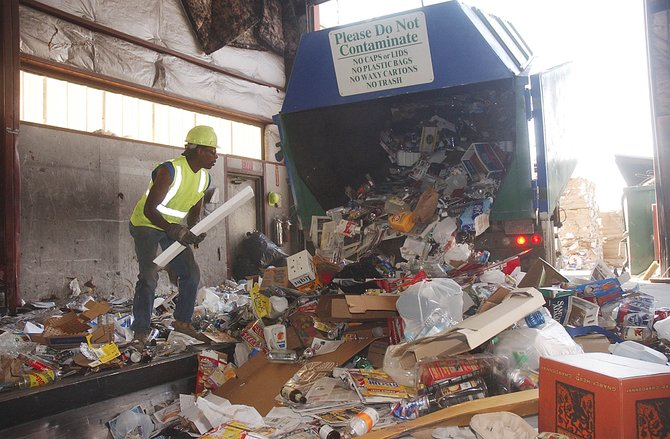 Waste Management employee Thomas Johnson looks for styrofoam as the Green Machine mobile recycling center is emptied Thursday at Waste Management. The Recycle America program, run by Waste Management, has expanded its recycling program.