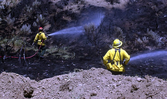 Craig Fire/Rescue members hose down the singed grass between Tri-State Equipment and the Black Nugget Motel. An unmarked electrical line caused the brush fire - as well as numerous power outages - at 2 p.m. Sunday.