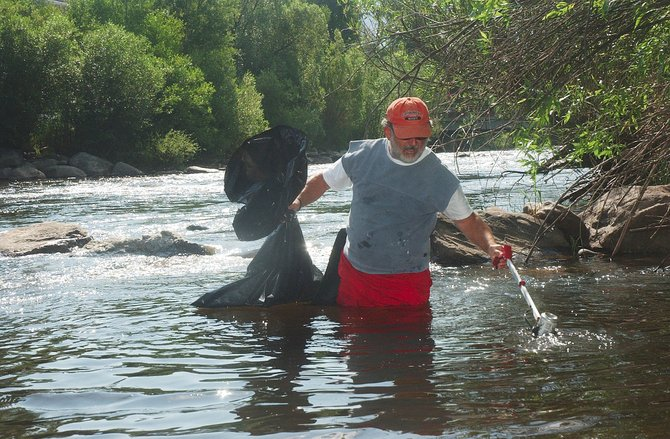 Part-time Steamboat Springs resident Jeff Henderson retrieves a beer can while picking up trash Monday in the Yampa River.