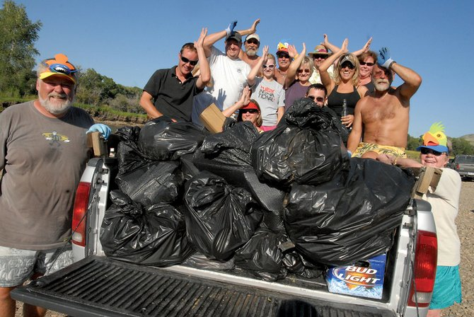 Members of the Northwest Colorado Chapter of Parrot Heads give a Parrot Head salute with the estimated 500 pounds of trash they picked up Tuesday at Pebble Beach. The group went on to collect trash in the Loudy-Simpson area, as well.