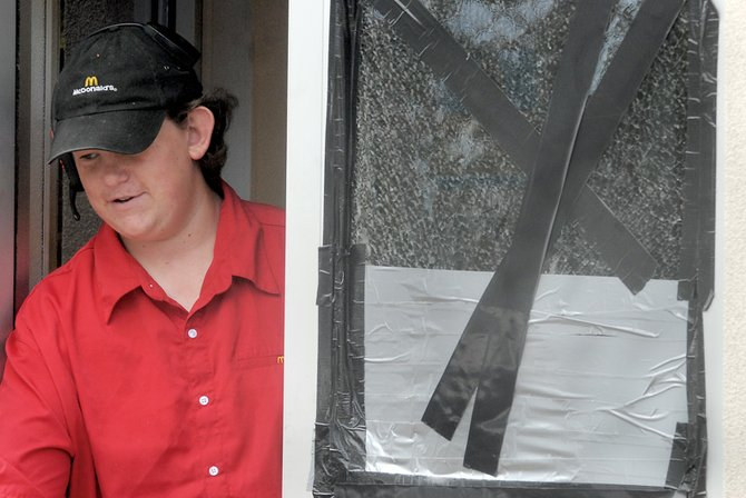 Jacob Templeton helps customers Wednesday in the McDonald's drive-through. The window was broken during the weekend when someone threw a rock through it.