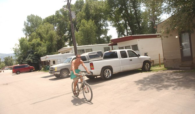 Steamboat Springs resident Mike Black rides through Dream Island Mobile Home Park on Wednesday.