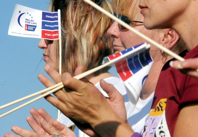 Yvonne McAnally, middle, and Amy Cashion, left, of team Live, Laugh and Love clap Friday during opening ceremonies of 2008 Craig Relay for Life. Thirty-nine teams, including more than 500 people, participated in the event that raised money for cancer research.