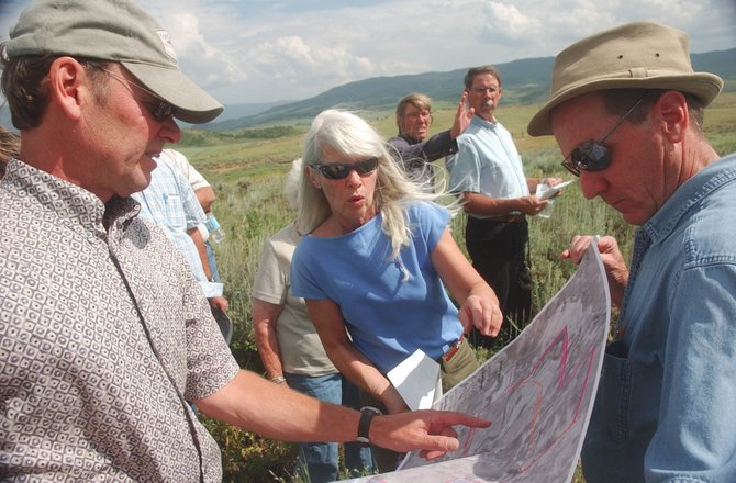 Land-use consultant Peter Patten, left, explains Steamboat 700 development property lines to Routt County Commissioner Diane Mitsch Bush on Thursday during a tour of five proposed development sites seeking amendments to the urban growth boundary. At right is Routt County Planning Commissioner Bill Norris.