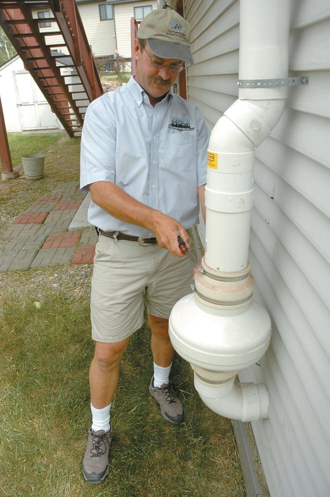 Greg Pohlman, a certified radon mitigation provider, inspects a fan system he installed outside a home in Heritage Park. Radon is found in high levels in about half the homes in Steamboat Springs, he said.