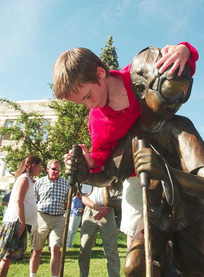 Six-year-old Lowen Epstein of Steamboat Springs plays on part of a bronze statue that was unveiled Wednesday in front of the Routt County Courthouse.