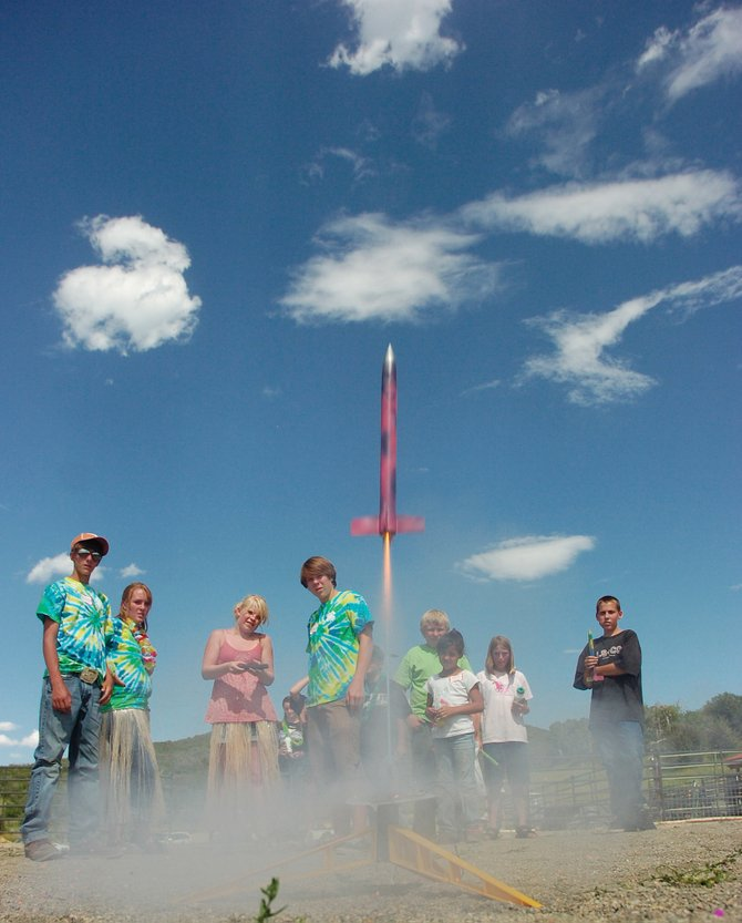 Routt County 4-H member Mackenzie Holmberg, 12, launches a rocket Thursday while other 4-H members watch during a 4-H Fun Day at the Circle K Ranch owned by the Kvols family.  For story, see page 4.