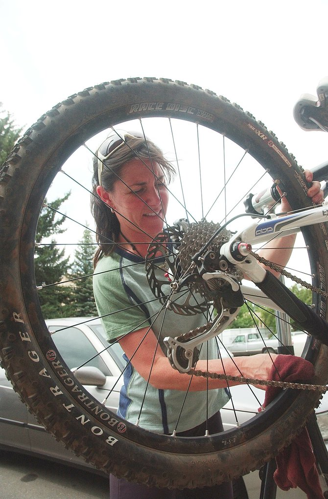 Steamboat Ski & Bike Kare employee Cindy Karet cleans her bike Wednesday outside of the shop.