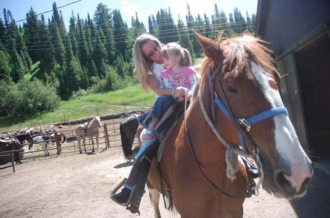 Four-year-old Kylie Smith gets ready to go horseback riding on Emerald Mountain on Thursday with her mom, Pam Smith, of Centennial.
