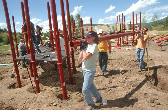 Alexis and Alex Wolf carry a piece of playground Friday while volunteering to build a new universal playground for children of all abilities at Strawberry Park Elementary School. Volunteers are still needed this weekend at Strawberry Park and Soda Creek elementary schools.