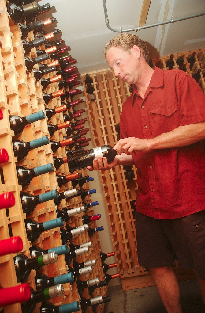 Mike Lang with Harwigs/L'apogee shelves wine Friday in the restaurant's wine cellar.