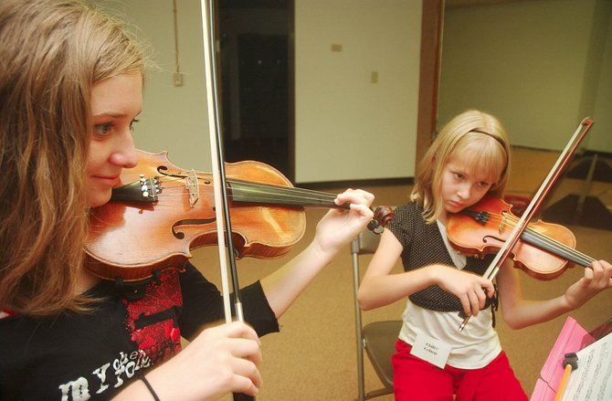 Fourteen-year-old Maddie Traverse and 11-year-old Claire Cohen rehearse during the Rocky Mountain Summer Conservatory.